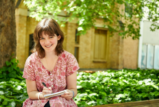 Sophie-sitting-outdoors-holding-pen-and-notebook