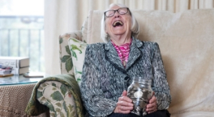 Elderly woman with money jar laughing